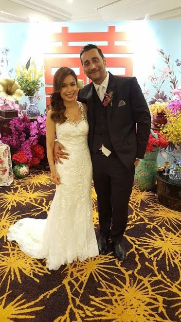 The delighted bride and groom strike a pose at their wedding reception at Ritz Carlton, KL